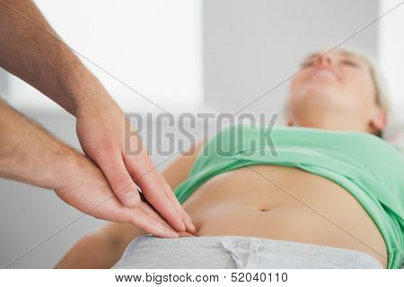 Physiotherapist pressing patients pelvis in bright office