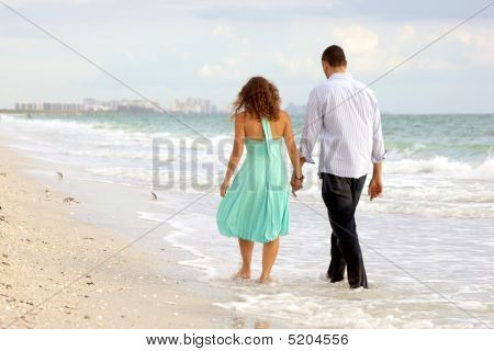 Young Couple Walking Hand In Hand On The Beach Thier Feet In The Water