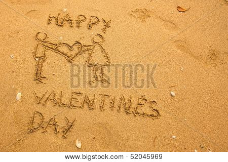 Happy Valentine's Day and a pair holding a big heart - texture on the sand.
