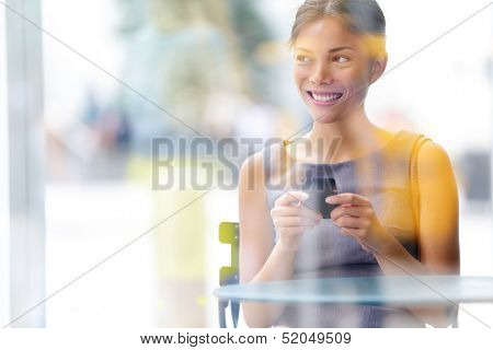City lifestyle business woman using smartphone on cafe. Young professional female businesswoman on smart phone while sitting indoors in cafe looking out. Multicultural Asian Caucasian girl in her 20s.