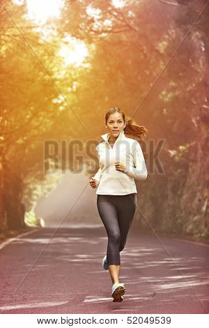 Young woman running. Female runner jogging on misty road with the early morning at sunrise with sun breaking through the trees as she trains during a fitness workout.