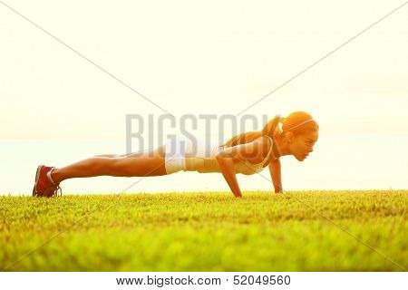 Push ups or press ups exercise by young woman. Girl working out on grass crossfit strength training in the glow of the morning sun against a white sky with copyspace. Mixed race Asian Caucasian model.