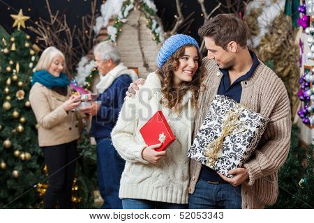 Happy young couple holding Christmas presents with parents standing in background at store