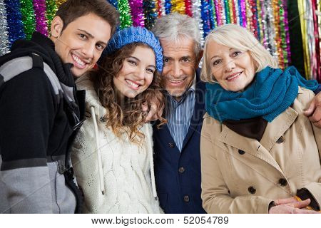 Portrait of happy family standing together against tinsels at store