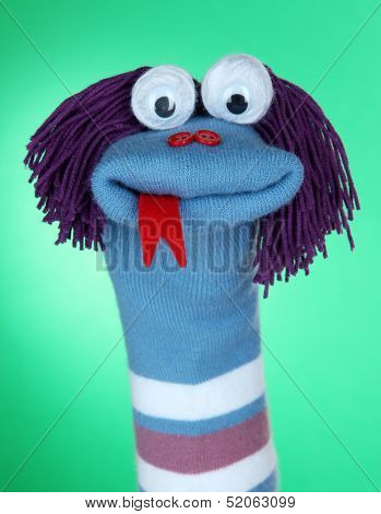 Cute sock puppet on green background