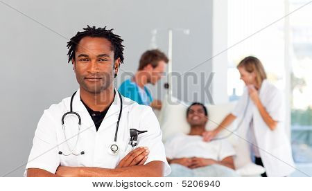 Serious Doctor With Folded Arms And Patient In The Background