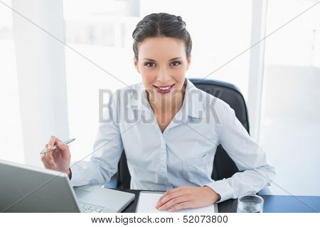 Happy stylish brunette businesswoman taking notes and looking at camera in bright office