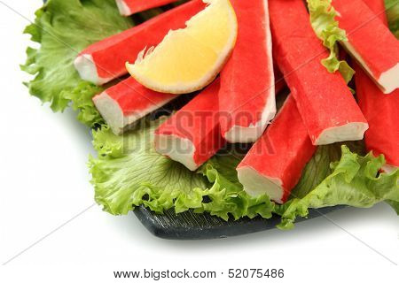 Crab sticks with lettuce leaves and lemon on plate isolated on white