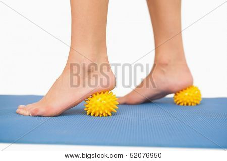 Close up of female feet touching massage ball on blue floor