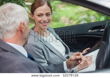Smiling partners working together in classy car on a bright day
