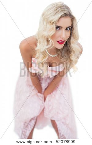 Dreamy blonde model in pink dress posing hands on the thighs on white background