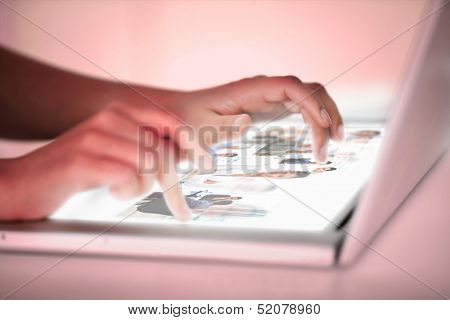 Close up of hands choosing pictures on a futuristic laptop on red background