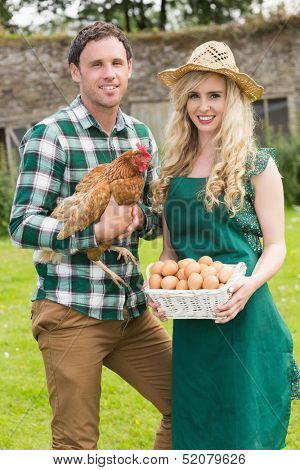 Happy young couple holding chicken and basket of eggs in their garden