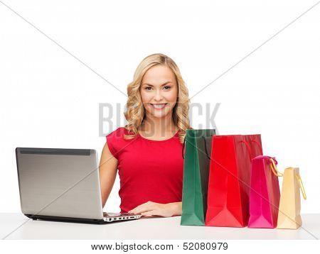 christmas, x-mas, online shopping concept - woman with shopping bags and laptop computer