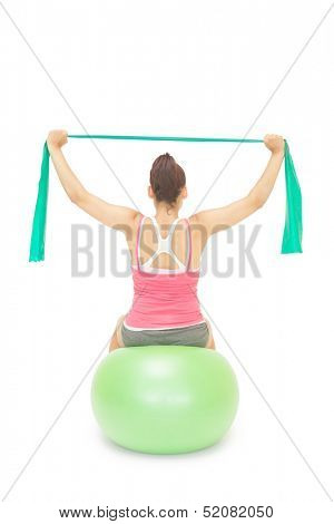 Sporty brunette stretching with resistance band sitting on exercise ball on white background