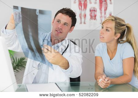 Content doctor showing a patient something on x-ray in bright office