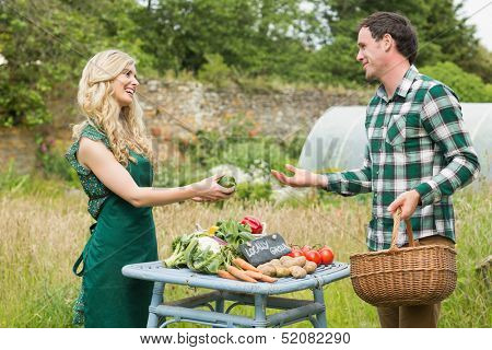 Young female farmer selling some vegetables to a cute man at farmers market