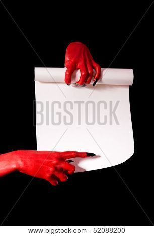 Red devil hands with black nails holding paper scroll and pointing at signature place