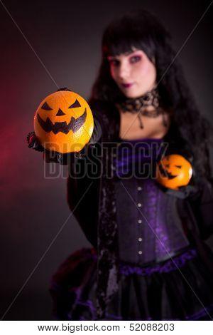 Beautiful witch holding Jack lantern oranges, selective focus on fruits