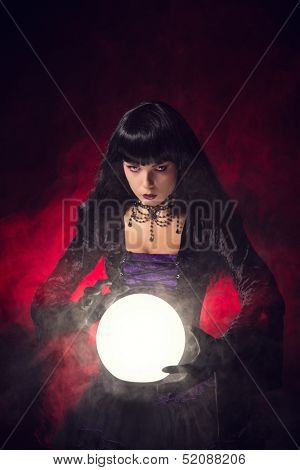 Beautiful gothic style fortune teller with a crystal ball, studio shot over smoky background