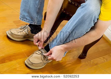 Man Putting On Shoes While Sitting On Footstool