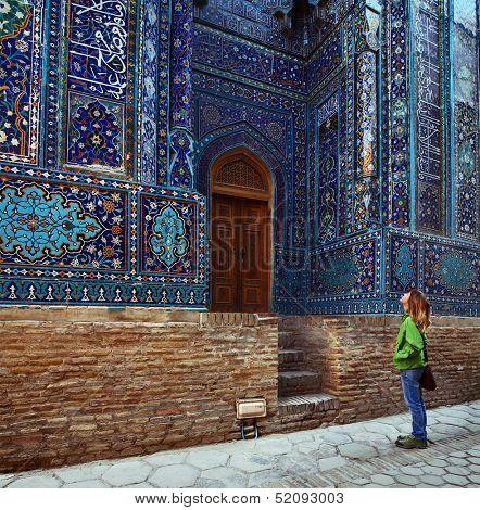 Young lady tourist watching ancient ornament of ancient complex of Shah i Zinda. Samarkand, Uzbekistan