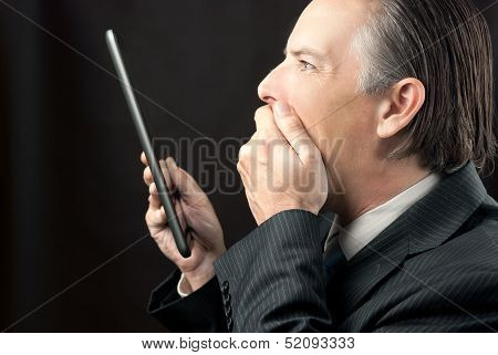 Businessman Looks At His Tablet Amazed