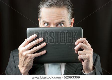 Businessman Peeks Over His Tablet