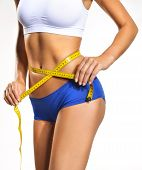 stock photo of nudity  - silhouette white woman in blue underwear with yellow tape measure - JPG