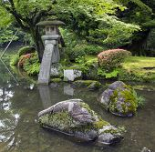 Fragment Of Japanese Garden With Stone Lantern And Big Mossy Rocks Standing In The Pond