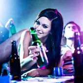 stock photo of social housing  - girl at drug fueled house party with beer bottle - JPG
