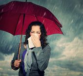 stock photo of rainy weather  - Sneezing Woman with Umbrella over Autumn Rain Background - JPG
