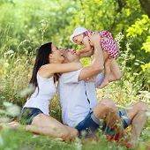 stock photo of father time  - Happy young family spending time together in green nature - JPG