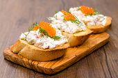 stock photo of baguette  - Italian Crostini with smoked salmon curd and trout caviar on a wooden board - JPG