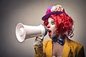 stock photo of circus clown  - beautiful clown speaking with megaphone - JPG