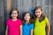 Sister and friends kid girls portrait smiling happy on gray fence wood backyard