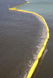 stock photo of water pollution  - pollution control barrier in the sea viewed from the city pier - JPG