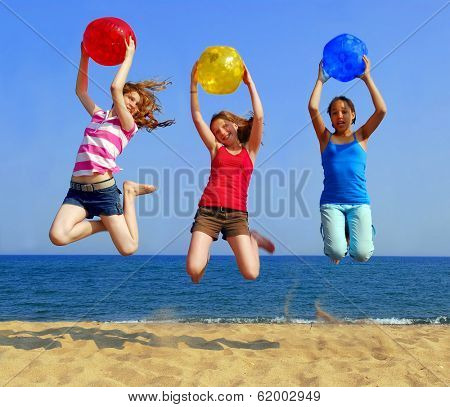 Three girls with colorful beach balls jumping on a seashore