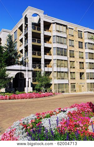 View of modern upscale condominium building with landscaping