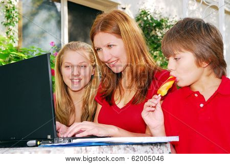 Mature woman working on computer at home with her children