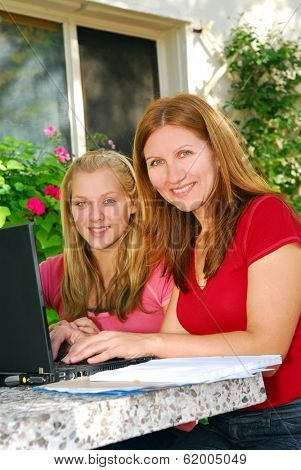 Mother and daughter working on computer at home in the backyard