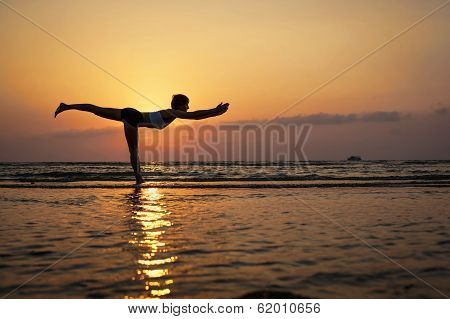 Yoga virabhadrasana III pose by woman in silhouette with sunset sky background
