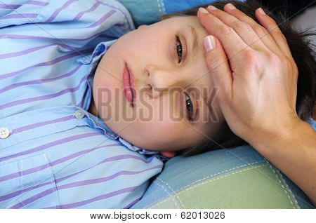 Mother's hand feeling the forehead of a sick child