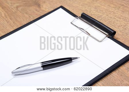Close Up Of Clipboard And Pen On Wooden Table