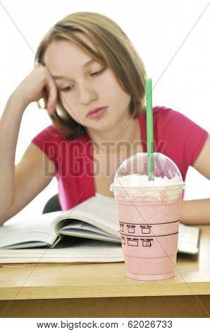 Teenage school girl studying with a milkshake