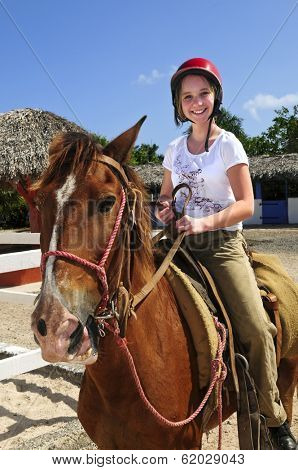 Young girl riding brown horse wearing helmet