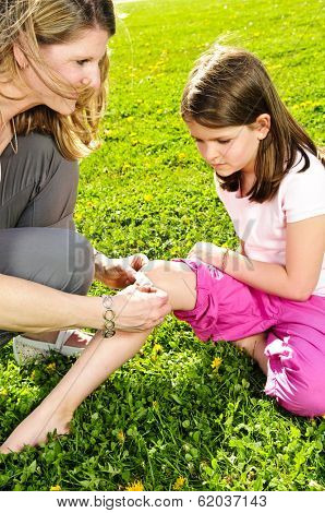 Portrait of mother giving first aid to daughters cut knee