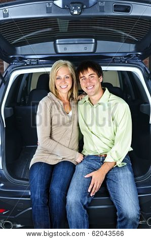 Happy young couple sitting at back of car