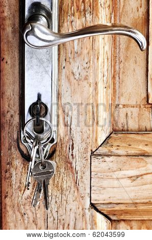 Set of keys in lock of old wooden door