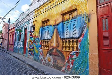 A wall painting of a man's head with moustache and sunglasses.
